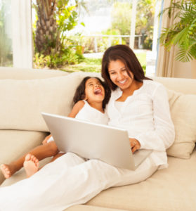 Mother And Daughter Surfing Net On Laptop